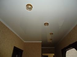 Белый глянцевый натяжной потолок в коридоре со светильниками. Панельный дом.