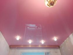 Розовый натяжной потолок со светильниками и карнизом